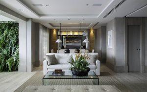 Integrados, os ambientes sociais ganharam elegância com piso travertino e contemporaneidade com parede de cimento queimado e marcenaria com tonalização especial, em tom acizentado.